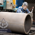 Grinding a piece of pipe that will eventually combine chrome white iron and steel