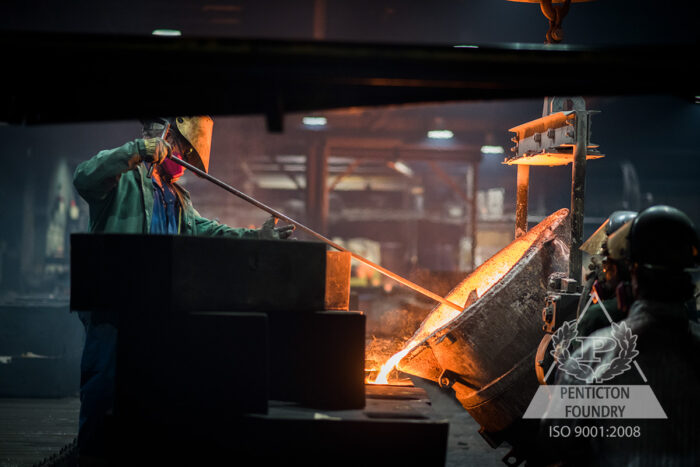 A foundry worker pours ASTM A536 120 – 90 – 02 ductile iron